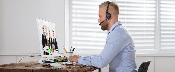 praca zdalna - mężczyzna siedzący przy biurku i pracujący na komputerze