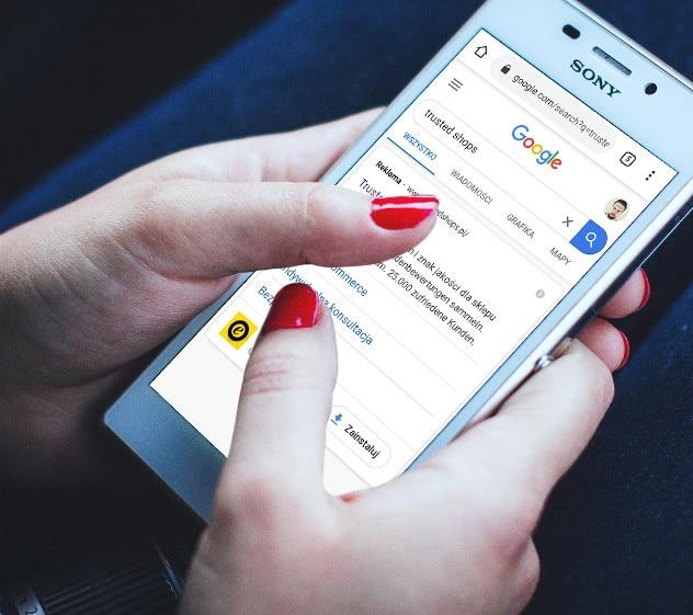 Na obrazku widać dłoń operującą smartfonem. Na smartfonie wyświetla się wynik wyszukiwania z reklamą Trusted Shops.