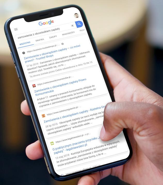 Na obrazku widać dłoń operującą smartfonem. Na smartfonie wyświetla się przykładowy wynik wyszukiwania. Obok wyników wyszukiwania można dostrzec różne favicony.