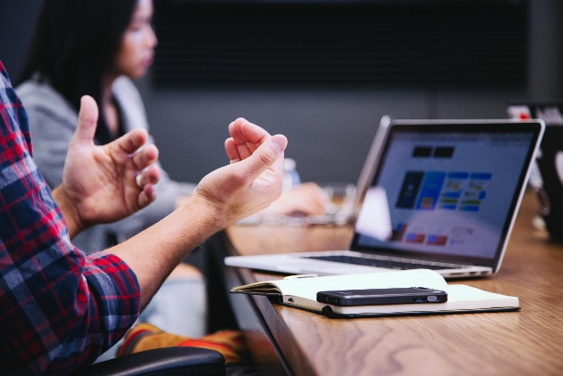 Zdjęcie pokazuje specjalistę przy laptopie w trakcie spotkania biznesowego.